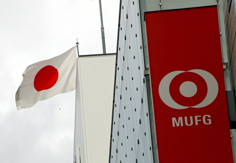 FILE PHOTO: Japan's national flag is seen behind the logo of  Mitsubishi UFJ Financial Group Inc (MUFG) at its bank branch in Tokyo