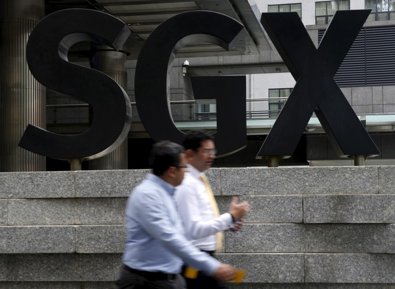 eaA man passes a Singapore Exchange (SGX) sign at the central business district in Singapore