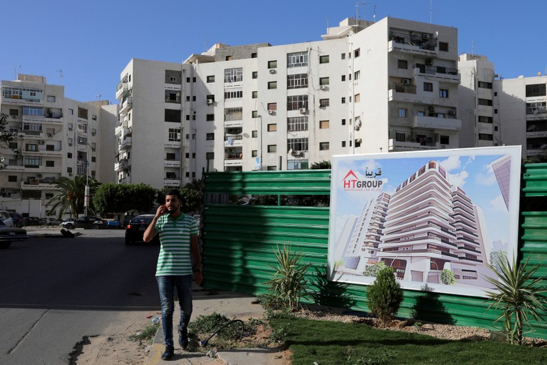 A man walks npast a banner advertising for buildings that will be built, in Tripoli