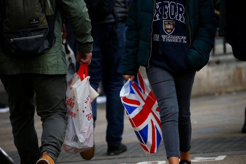 Shoppers carry shopping in plastic bags in the West End, in London