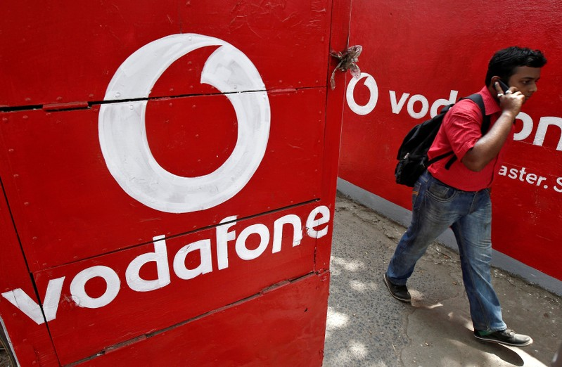 FILE PHOTO: Man speaks on his mobile phone as he walks past the logos of Vodafone painted on a roadside wall in Kolkata