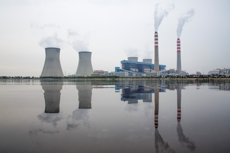 A power station of the State Development & Investment Corporation (SDIC) is reflected in a lake in Tangshan