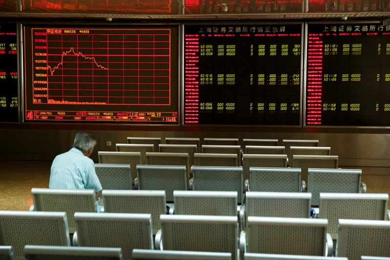 A man sits in front of a board showing market information at a securities brokerage house in Beijing
