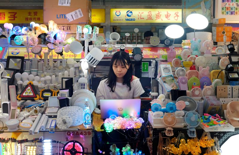 Woman works at a stall inside an electronics mall on Huaqiangbei Commercial Street in Shenzhen