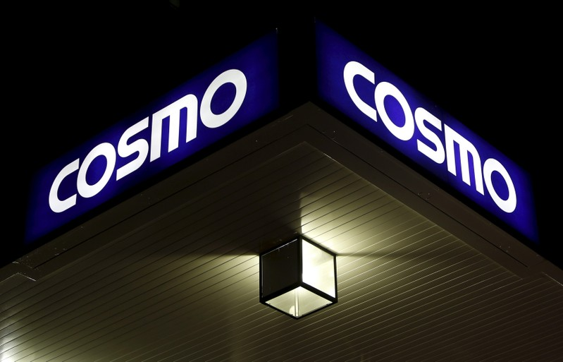 A light is seen under a signboard of Cosmo Energy Holdings' Cosmo Oil service station in Tokyo
