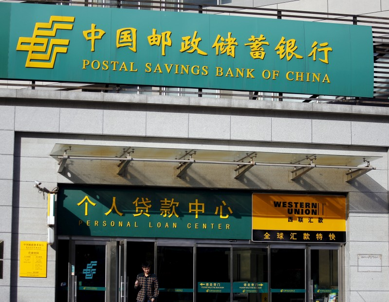 Man walks out of a Postal Savings Bank of China branch in Beijing