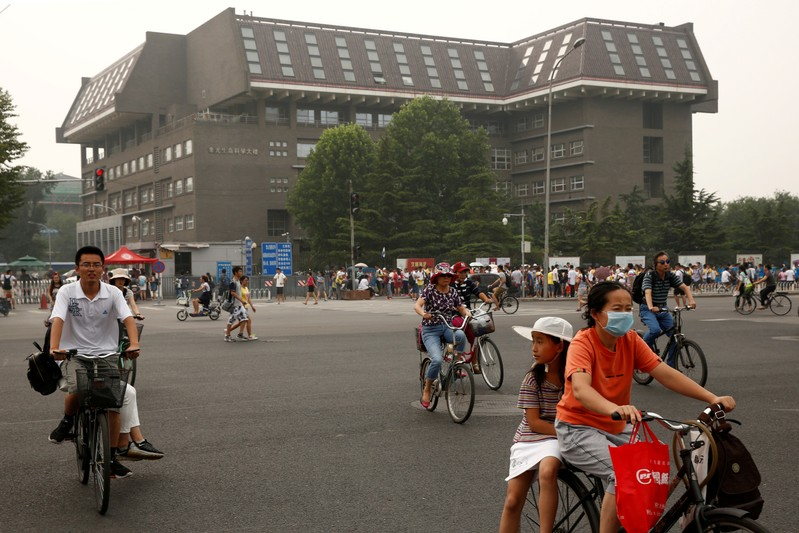 People cycle past a building in Peking University in Beijing