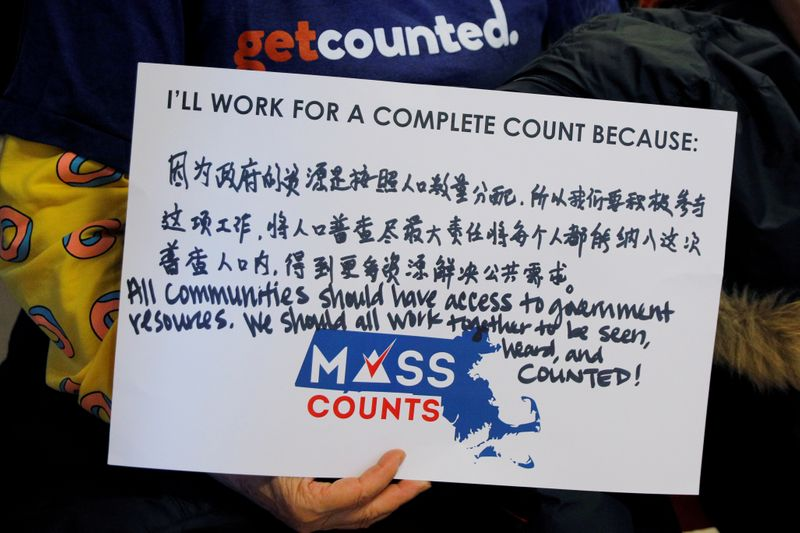 FILE PHOTO: A community activist holds a sign in Chinese and English at an event to mark the one-year-out launch of the 2020 Census efforts in Boston