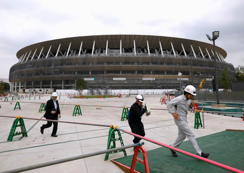 FILE PHOTO: Workers are seen at the construction site of the New National Stadium, the main stadium of Tokyo 2020 Olympics and Paralympics, during a media opportunity in Tokyo, Japan