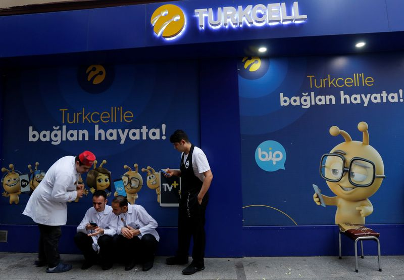 Men look at the screens of their mobile phones outside a Turkcell shop in Istanbul