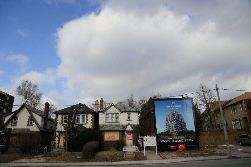 FILE PHOTO:  A real estate assembly of houses marked for demolition stand next to a billboard advertising a future condominium in Toronto