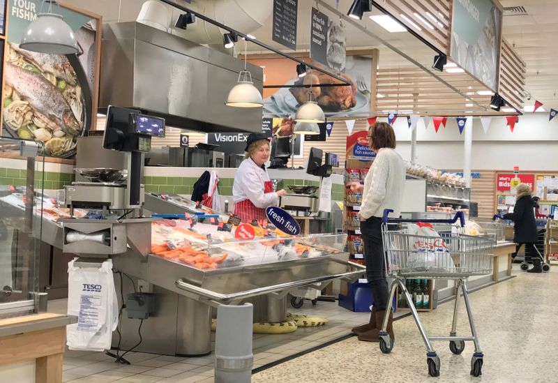 A customer talks to an in store fishmonger at a Tesco supermarket near Liverpool