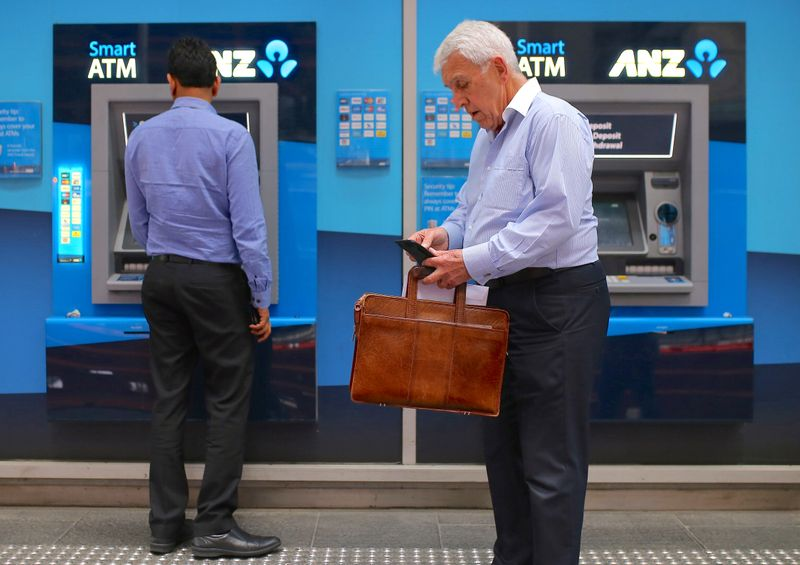 Customers stand next to automatic tellar machines located outside a branch of the Australia and New Zealand Banking Group (ANZ) in central Sydney