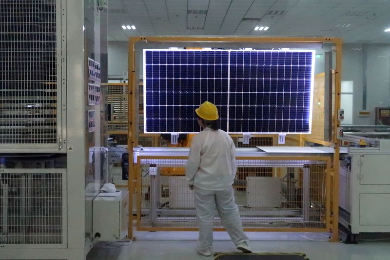 Worker conducts quality-check of a solar module product at a factory of a monocrystalline silicon solar equipment manufacturer in Xian, Shaanxi