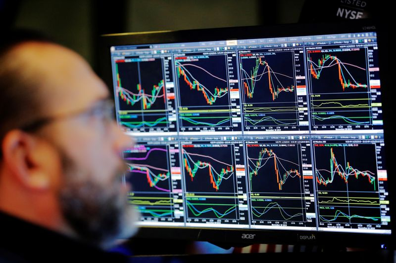 FILE PHOTO:  A trader works on the floor of the New York Stock Exchange shortly after the opening bell in New York City