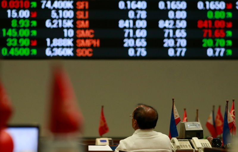 A stockbroker looks at the electronic board inside the Philippine Stock Exchange (PSE) in Makati city, metro Manila