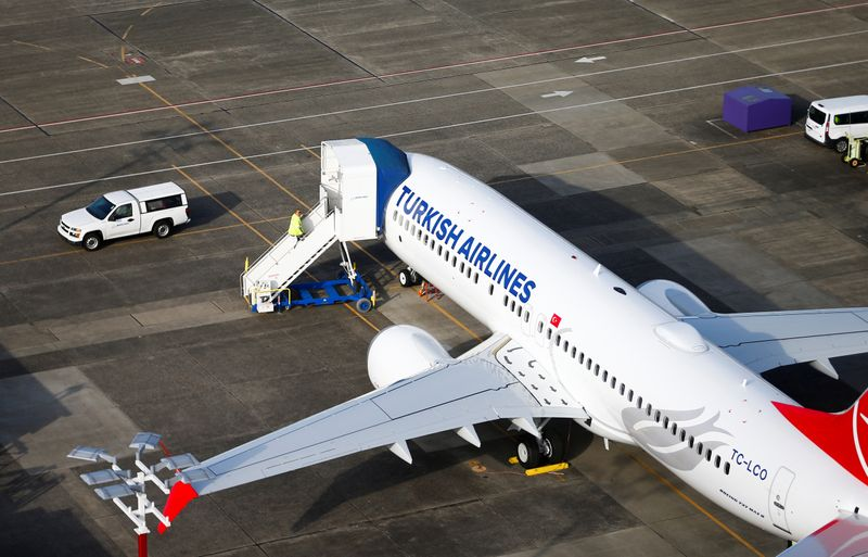 An aerial photo shows a worker climbing up to a Turkish Airlines Boeing 737 MAX airplane grounded at Boeing Field in Seattl