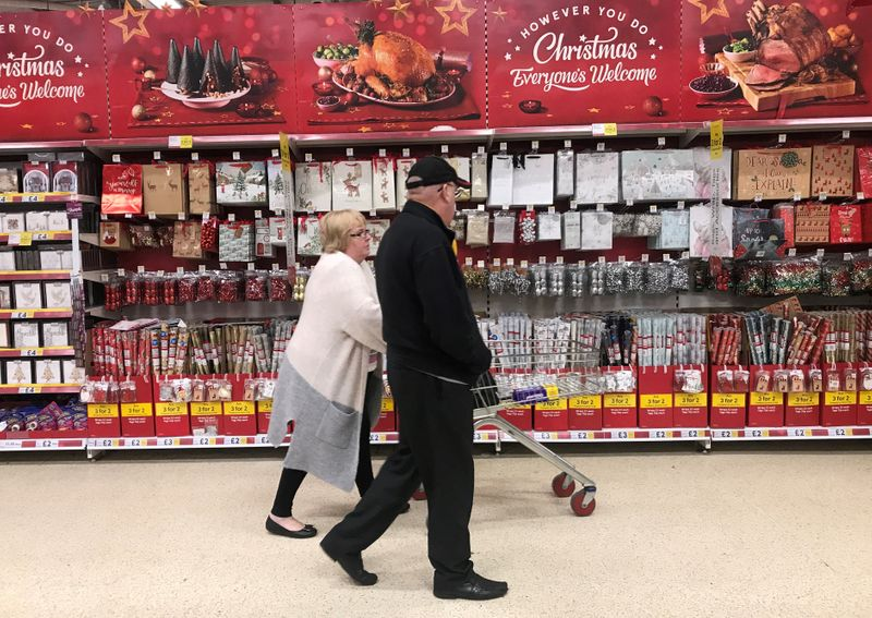 FILE PHOTO: A woman pushes a shopping trolley past Christmas decorations for sale in a Tesco store in Manchester