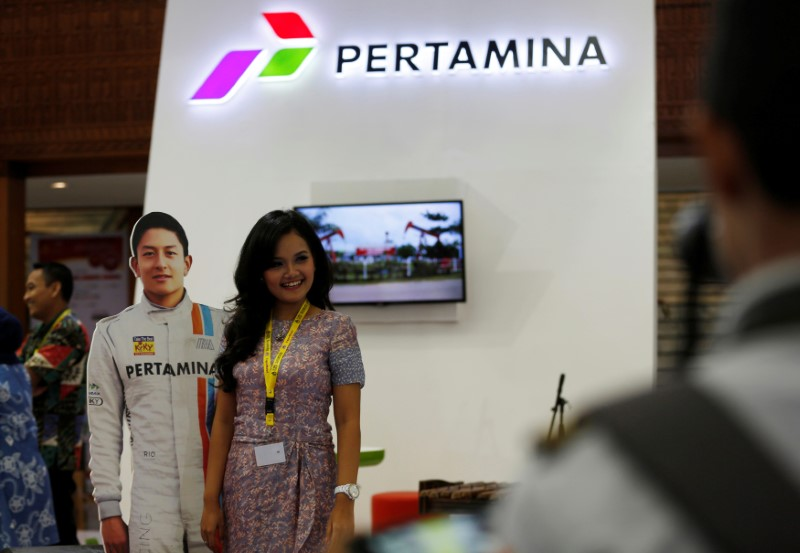 A woman has her picture taken with a cut out of Formula One driver Rio Haryanto at state-owned oil giant Pertamina's booth at the Indonesia Petroleum Association Convention and Exhibition in Jakarta, Indonesia