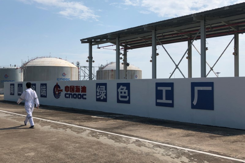 Worker walks past the logo of China National Offshore Oil Corporation (CNOOC) at its Nanshan liquefied natural gas (LNG) terminal in Hainan