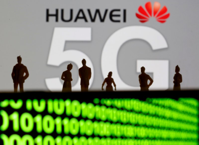 FILE PHOTO: Small toy figures are seen in front of a displayed Huawei and 5G network logo in this illustration picture