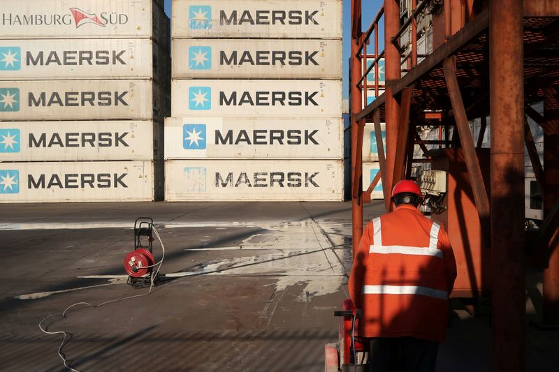 FILE PHOTO: Worker is seen next to Maersk shipping containers at a logistics center near Tianjin por