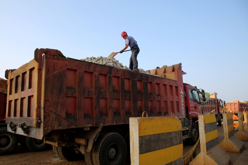 A man works on transporting iron ore on a truck at Ganyu port in Lianyungang