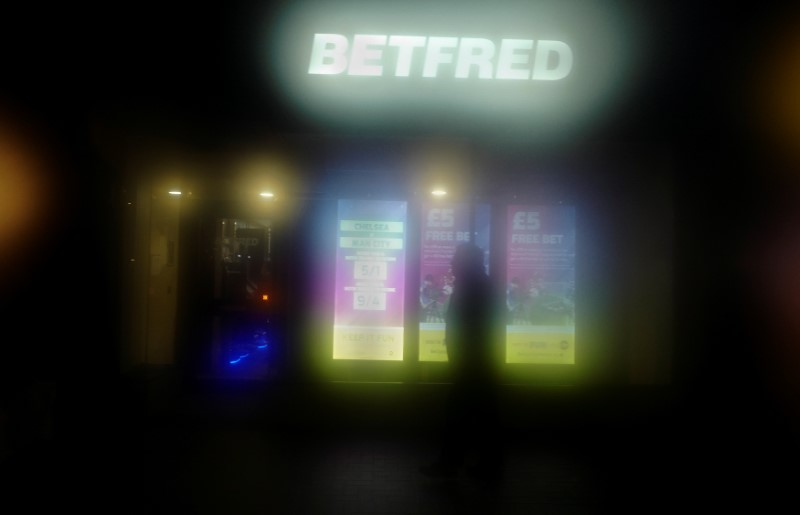 FILE PHOTO:  A man is seen through a misty bus window passing a Betfred betting shop in London