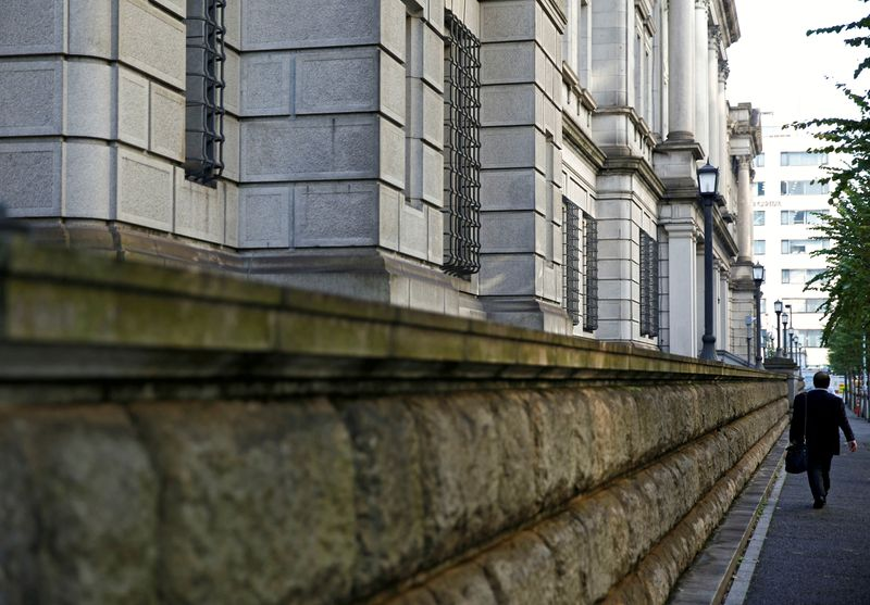 FILE PHOTO: A man walks past the Bank of Japan building in Tokyo