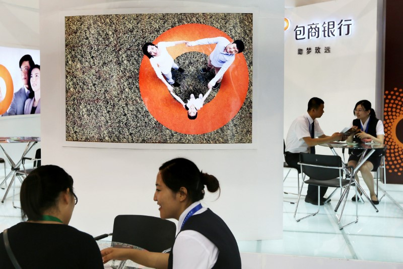 Staff members are seen at the booth of Baoshang Bank at an investment and finance fair for small and medium sized enterprises in Beijing