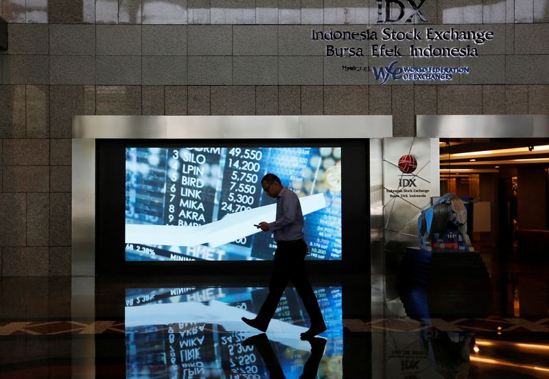 A man walks past screen at the Indonesia Stock Exchange building in Jakarta