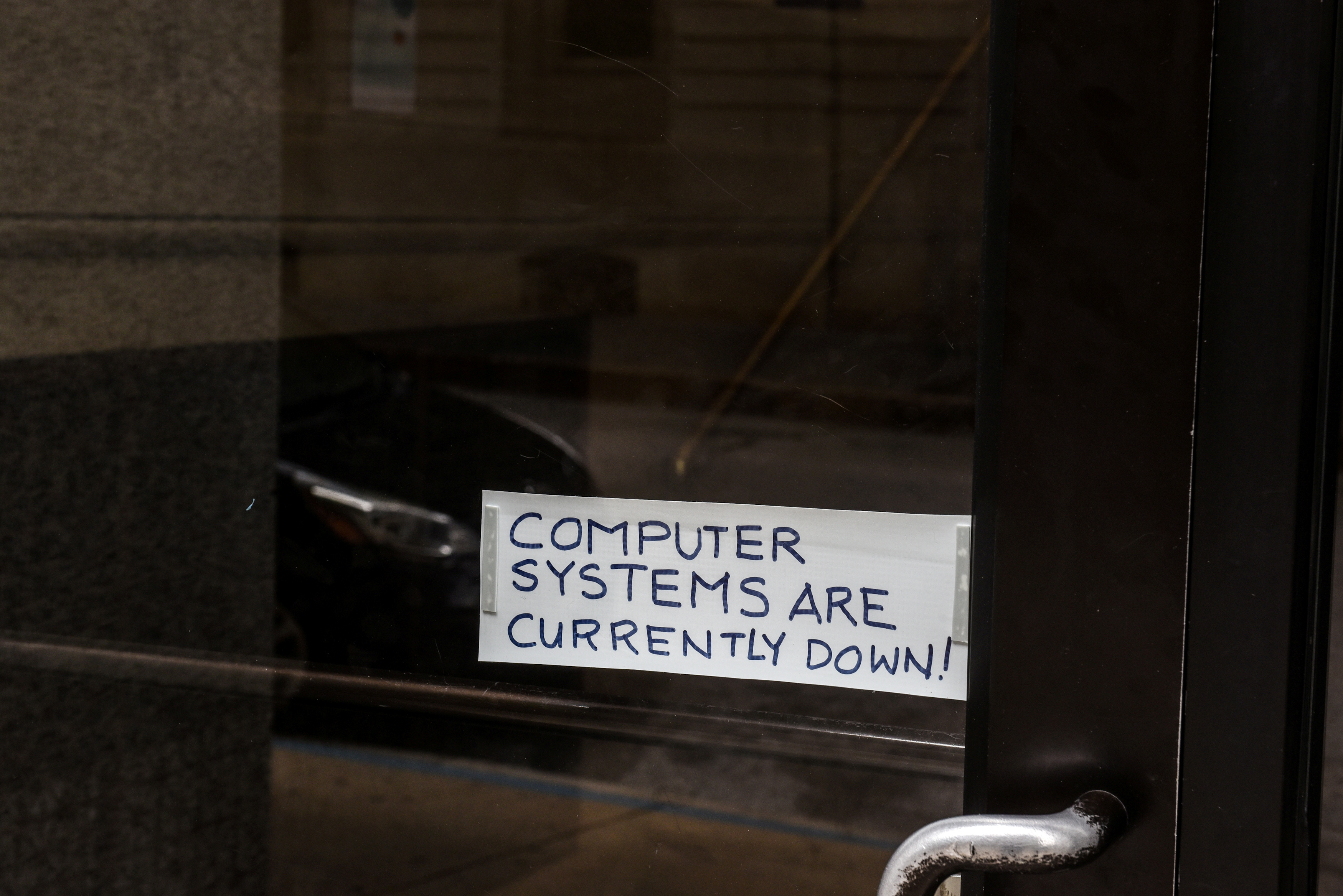 FILE PHOTO: A sign referring to the hacked computer system of Baltimore City is taped to a door near Baltimore City Hall in Baltimore, Maryland