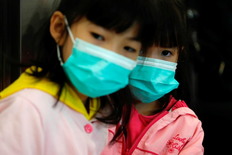Children wear masks to prevent an outbreak of a new coronavirus at the Hong Kong West Kowloon High Speed Train Station, in Hong Kong