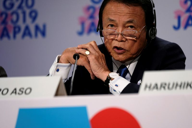 Japanese Finance Minister Taro Aso takes questions from reporters at the annual meetings of the International Monetary Fund and World Bank in Washington