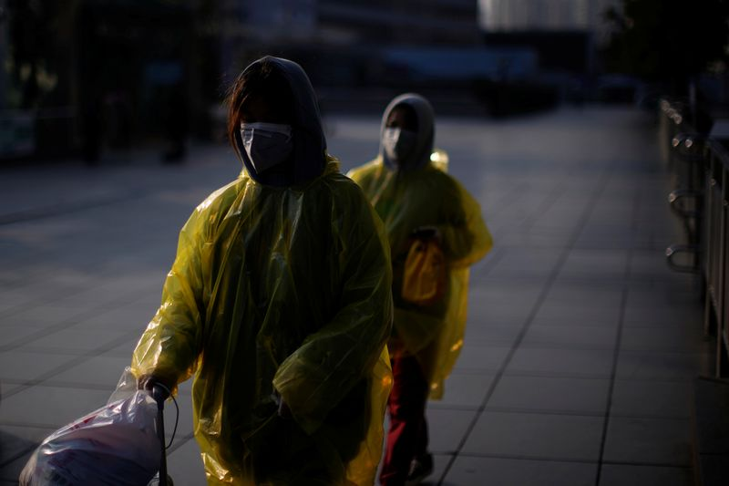 Women wearing masks and plastics rain coat as protection from a coronavirus are seen at the Shanghai railway station in Shanghai