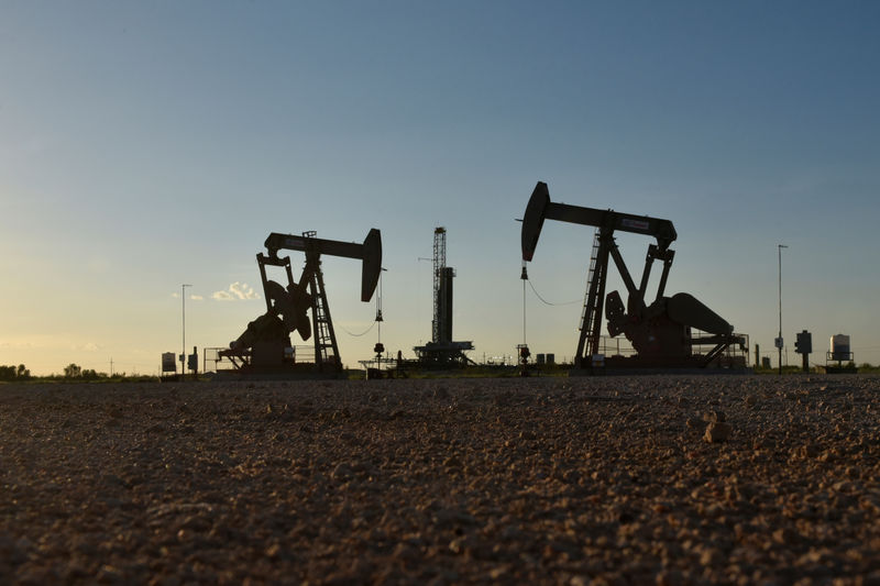 FILE PHOTO: Pump jacks operate in front of a drilling rig in an oil field in Midland