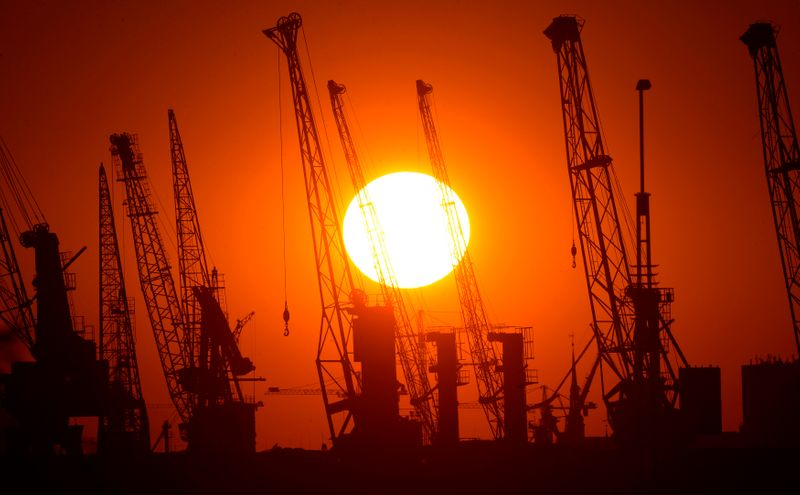 Cranes of German shipyard Blohm&Voss are silhouetted during sunset in Hamburg
