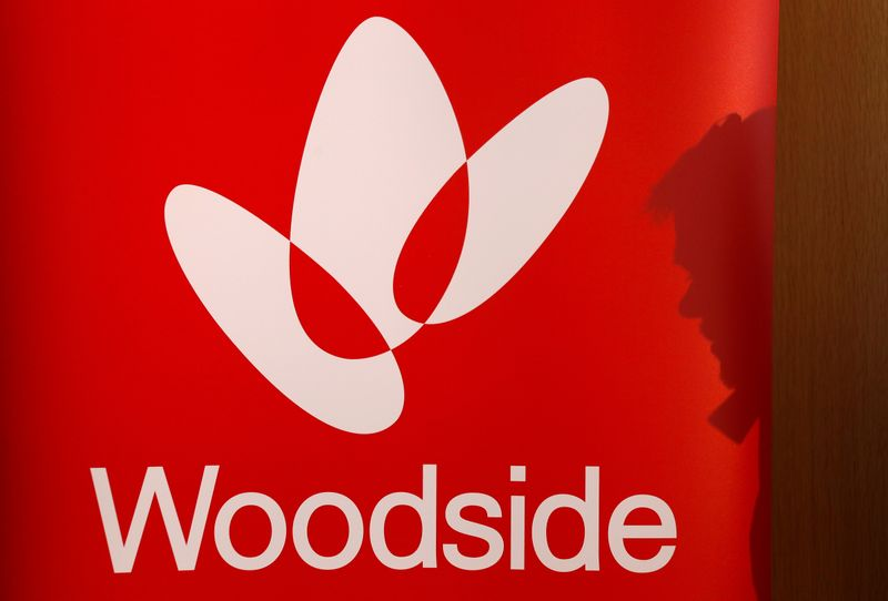 The shadow of a man is cast onto a poster displaying the logo for Woodside Petroleum, Australia's top independent oil and gas company, at a briefing for investors in Sydney,