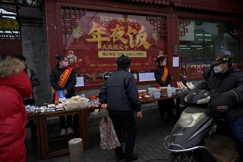 Staff members wearing face masks stand next to a stall set up by a restaurant outside its outlet in Beijing