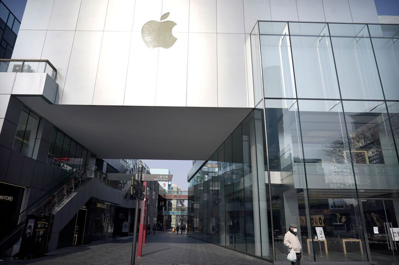 Man wearing a face mask walks past a closed Apple store at Sanlitun in Beijing