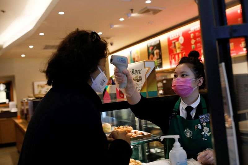 FILE PHOTO: Worker uses a thermometer to check the temperature of a customer as she enters a Starbucks shop as the country is hit by an outbreak of the new coronavirus, in Beijing