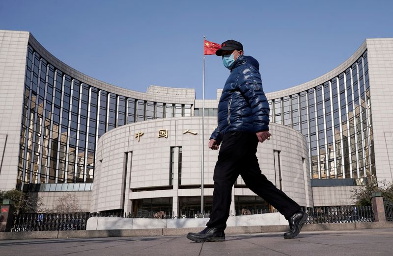 Man wearing a mask walks past the headquarters of the People's Bank of China, the central bank, in Beijing