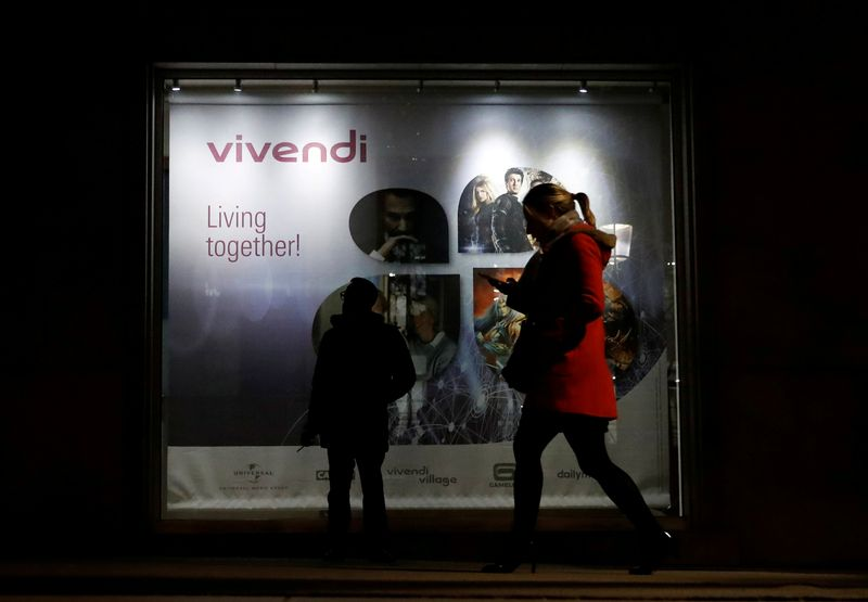 FILE PHOTO: A man stands as a woman walks past a sign of Vivendi at the main entrance of the entertainment-to-telecoms conglomerate headquarters in Paris