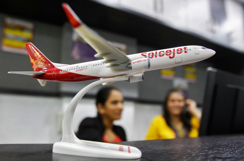 Employees work inside a travel agency office besides a model of a SpiceJet aircraft in Ahmedabad