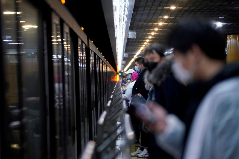 FILE PHOTO: People wearing face masks are seen at a subway station in the morning after the extended Lunar New Year holiday caused by the novel coronavirus outbreak, in Shanghai