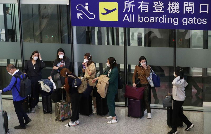 FILE PHOTO:  Passengers wear protective masks as they wait at Hong Kong International Airport, following the coronavirus outbreak in Hong Kong