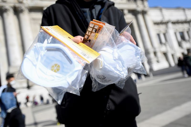 FILE PHOTO: A street vendor sells face masks outside the central railway station in Milan