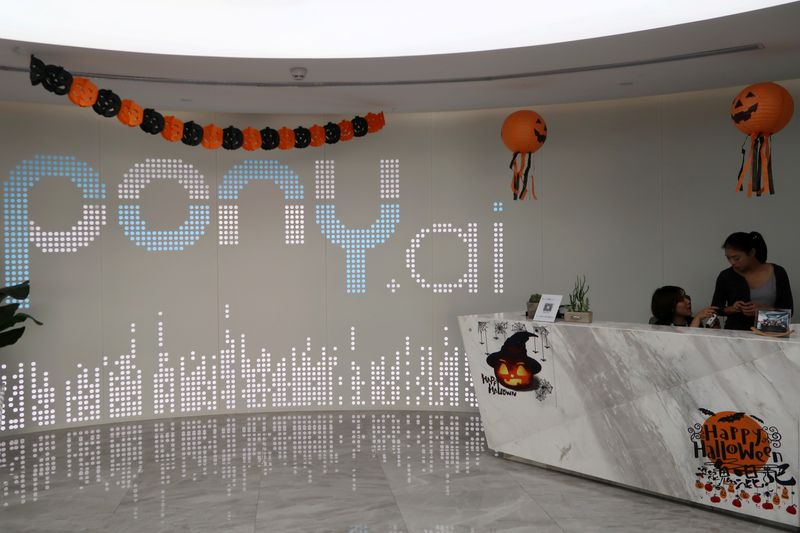 Staff members are seen at the Halloween-decorated reception area of the Chinese self-driving startup Pony.ai headquarters in Guangzhou