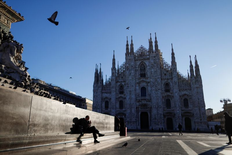 People walk through a near-empty Duomo square, usually full of people, as a coronavirus outbreak in northern Italy continues to grow, in Milan