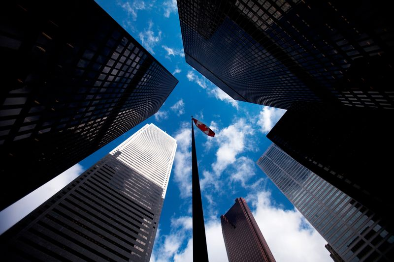 Skyscrapers loom over a flagpole carrying the Canadian flag in the financial district in Toronto